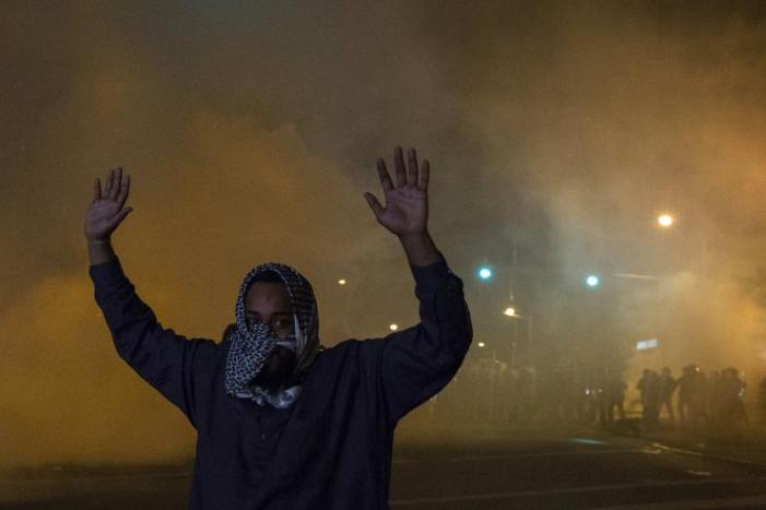 From: http://www.ibtimes.com/baltimore-uprising-2015-parents-black-males-opposite-sides-town-fear-police-1903525. A member of the Nation of Islam attempting to keep peace between protesters and riot police raises his hands amid clouds of smoke and gas used by riot police to disperse crowds. Baltimore, Maryland April 28, 2015. Reuters/Adrees Latif